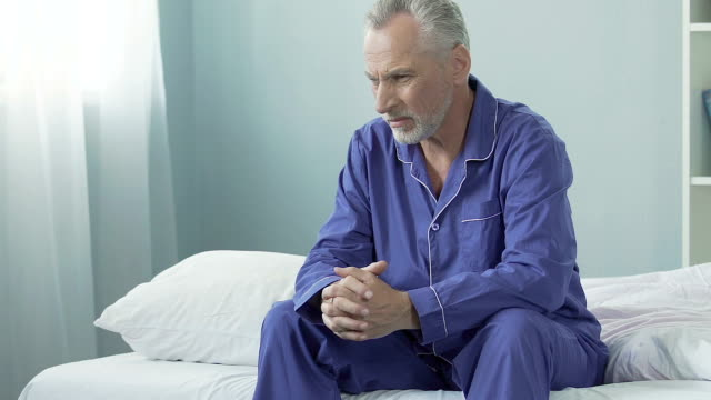 Angry old man sitting on bed, looking around suspiciously, dissatisfied, moody video