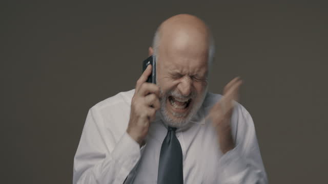 Angry senior businessman shouting on the phone