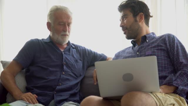 화가 선임 아버지와 성인 아들은 함께 집에서 방에 소파에 앉아 노트북 컴퓨터를 사용하여 주장 . 기술을 가진 2 세대 가족 남성 - 짜증 스톡 비디오 및 b-롤 화면