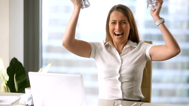 Angry stressed businesswoman throwing crumpled paper and screaming at workplace video