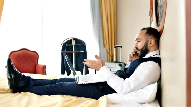 Angry stylish male businessman lying on bed at vintage hotel room having mobile conference
