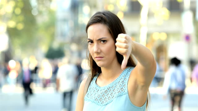 angry woman gesturing thumb down in the street - rabbia emozione negativa video stock e b–roll