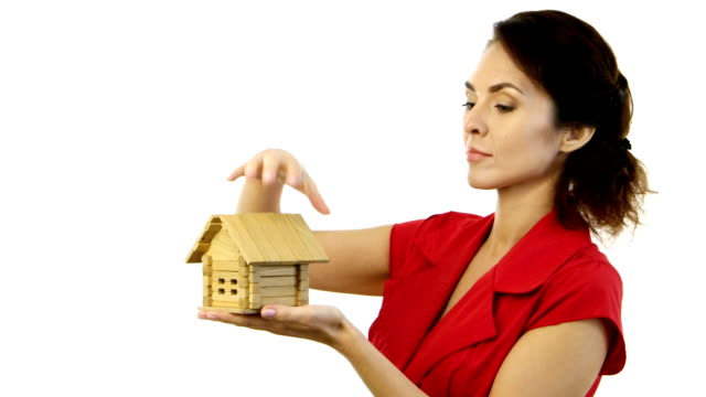 Angry woman holding a little house in her hands and destroy home video