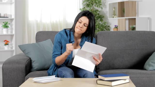 vídeos de stock e filmes b-roll de angry woman reading a letter at home - carta documento