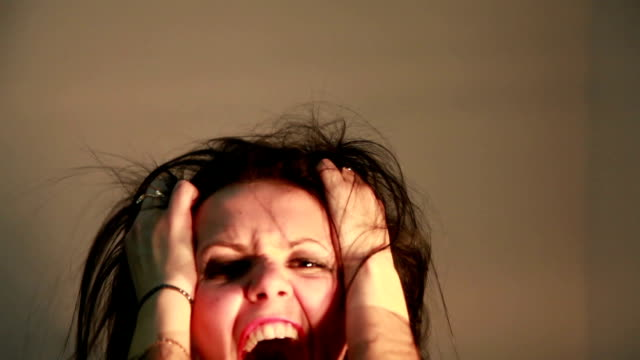 angry woman screaming and rending her hair in agony - spettinato video stock e b–roll