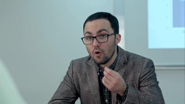机に座って怒っている若い男性教師と学生に話す ビデオ