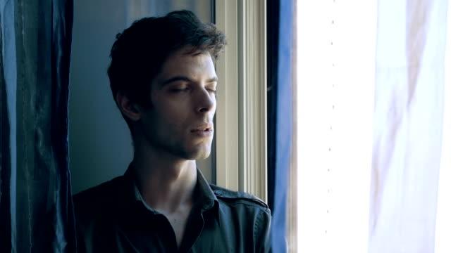 Hombre joven enojada, en sus problemas respiratorios cerca de la ventana - vídeo