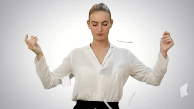 Angry young woman rips paper documents, throw it at the camera on white background video