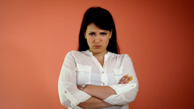 angry young woman standing isolated over pink background. Looking camera
