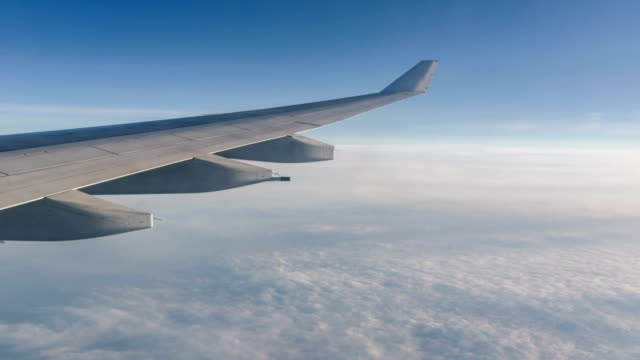 animated picture with cinemagraph effect of airplane flying in sky - skrzydło samolotu filmów i materiałów b-roll