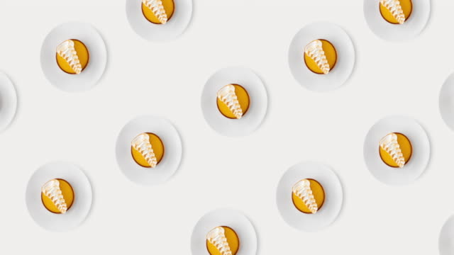 animated seamless pattern with many yellow round pastries with white milk cream on a plate isolated on a bright white background, top view - chrupkie ciasto filmów i materiałów b-roll
