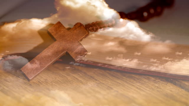 Animation of Christian cross over rosary beads, clouds with wooden surface in the background