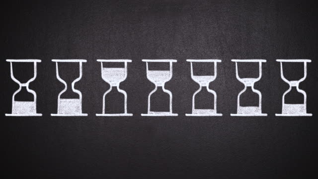 Animation of hourglasses with pouring sand drawn on blackboard video