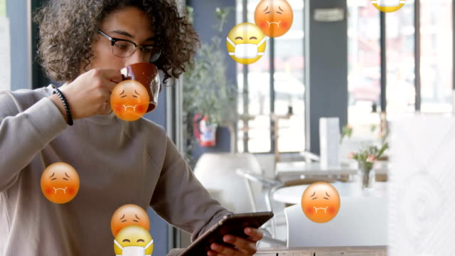 Animation of multiple emojis falling over a Caucasian man drinking a beverage