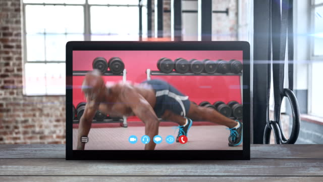 Animation of tablet computer showing a African American man exercising. Coronavirus  spreading