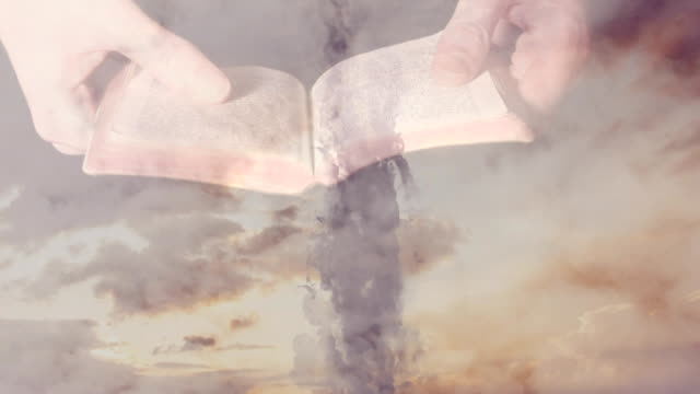 Animaton of Christian cross over a person holding the Bible