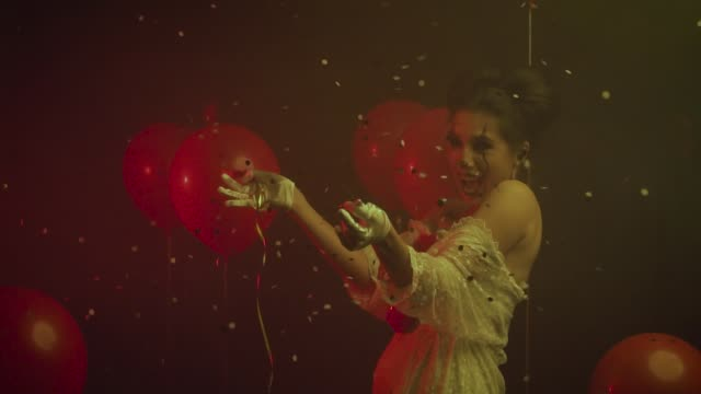 Animator woman clown bursts helium balloon pops with a needle, golden falling.