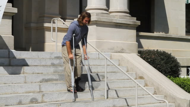 Ankle Brace Crutches Adult male patient descends steps at a public building while wearing an ankle brace and using crutches for support and stability. crutch stock videos & royalty-free footage