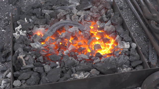 Annealing and heat-treating of iron horseshoe for forging. Annealing and heat-treating of iron horseshoe for forging. Embers glow in a iron forge. Static camera. wrought iron stock videos & royalty-free footage
