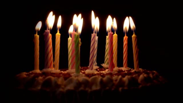 Anniversary cake, burning candles in dark