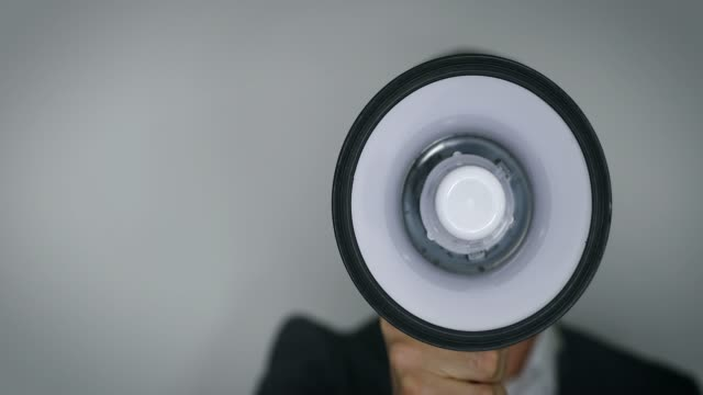 announcement - businessman with megaphone in front of face on gray background copy space announcement - businessman with megaphone in front of face on gray background copy space megaphone stock videos & royalty-free footage