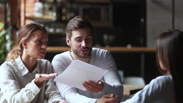 infastidito giovane coppia di clienti in possesso di documenti discutendo con il manager - rabbia emozione negativa video stock e b–roll