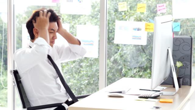 腹が立つアジア実業家コンピューター彼に問題があります。オフィスで壊れたコンピューターに問題を持っている人を強調しました。 - 悩む点の映像素材/bロール