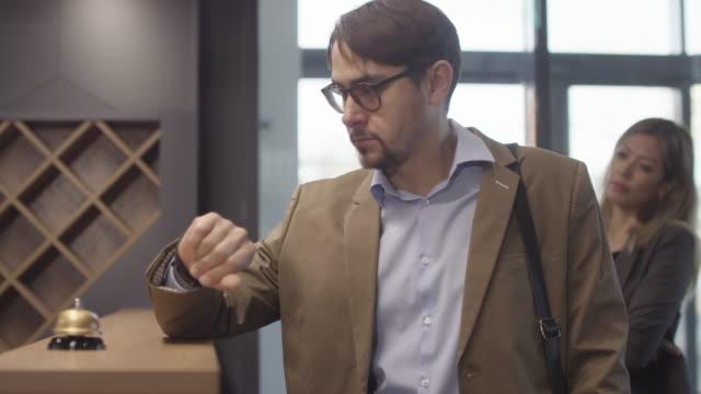 vidéos et rushes de l'homme contrarié sonnant la cloche au bureau de réception d'hôtel - faire la queue