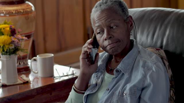 infastidito donna nera anziana rispondendo al suo cellulare - rispondere video stock e b–roll
