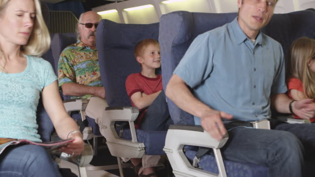 Annoying child on plane Annoying child on plane, kicking the seat back in front of him. seat stock videos & royalty-free footage