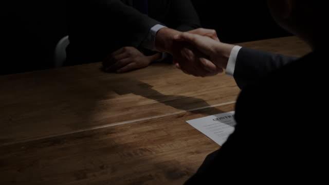 vidéos et rushes de partenaires d'affaires anonymes se serrant la main à la réunion secrète dans la salle noire - mystère