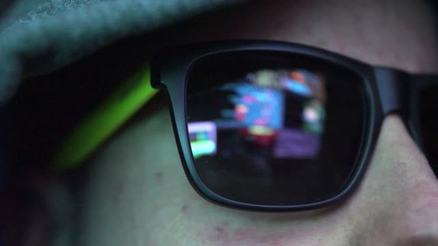 Anonymous Hacker in Dark Glasses Looking at Computer Screen Code Reflections