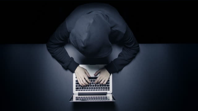 stockvideo's en b-roll-footage met anonieme hacker in het donker met laptop - onherkenbaar persoon