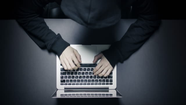 Anonymous hacker in the dark with laptop video