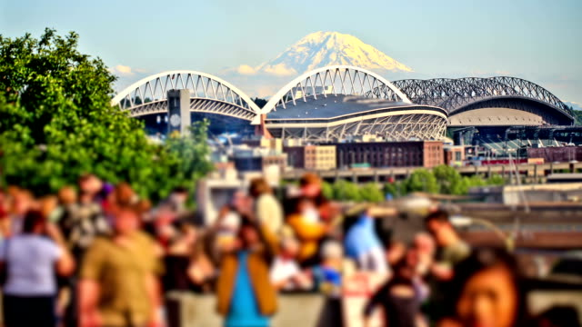 Anonymous Large Crowd Time Lapse Park v16. Anonymous large crowd time lapse at city park with beautiful background view of mountain and waterfront traffic. seattle stock videos & royalty-free footage