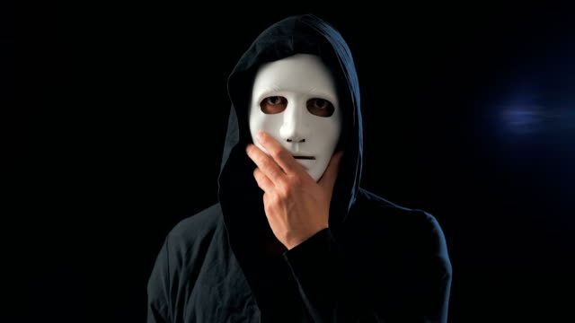 vídeos de stock e filmes b-roll de anonymous man in a white mask covering his face and a black hood turns and looks at the camera. black dark background. concept of a member of a secret organization - capuz