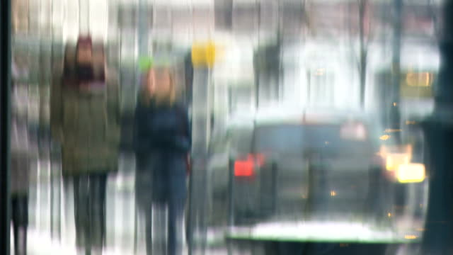 Bидео anonymous people walking in the street of a city with showcase reflections