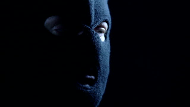anonymous person in black balaclava talking to camera - anonymous hackers stock videos and b-roll footage