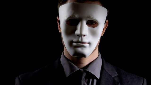 vídeos de stock e filmes b-roll de anonymous suit man in mask folding hands on black background, illegal activity - corruption
