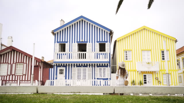vídeos de stock e filmes b-roll de anonymous woman looking at colorful buildings - aveiro