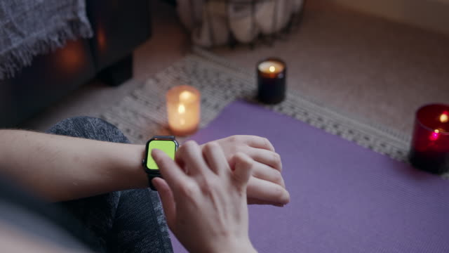 anonymous woman sitting using a green screen smart fitness watch during exercise - mindfulness filmów i materiałów b-roll