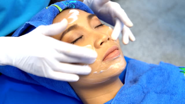 anti aging facial treatment with cream massage on woman face - collagene video stock e b–roll