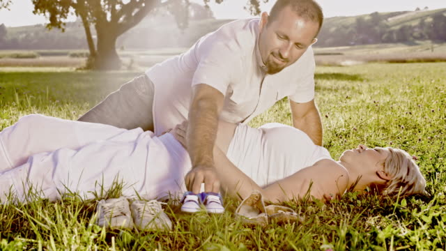 DS Anticipated couple expecting baby Dolly wide shot of a mid-adult man brings baby shoes to his pregnant wife while she is lying on the grass in countryside. baby booties stock videos & royalty-free footage