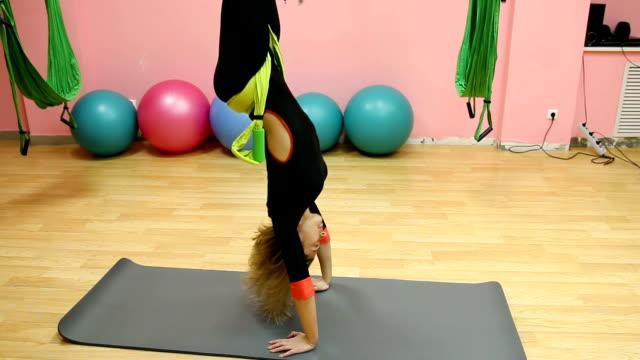 anti-gravity yoga, sportliche frau, die yoga übungen indoor - gymnastikanzug stock-videos und b-roll-filmmaterial