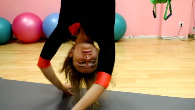 anti-gravity yoga, athletic woman doing yoga exercises indoor - trykot filmów i materiałów b-roll