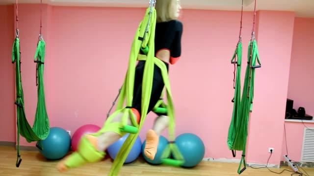 anti-gravitation yoga, atletisk kvinna gör yogaövningar inomhus - gympingdräkt bildbanksvideor och videomaterial från bakom kulisserna