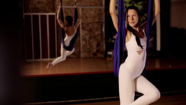 vidéos et rushes de anti-gravity yoga, femme faisant des exercices d'yoga intérieur - justaucorps