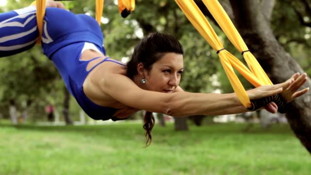 anti-schwerkraft-yoga, yoga-übungen mit hängematte im park frau - gymnastikanzug stock-videos und b-roll-filmmaterial