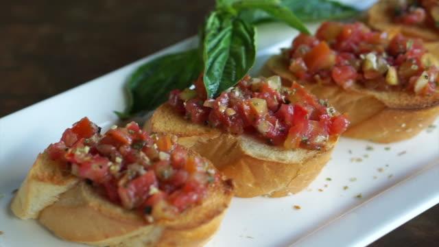 antipasto bruschetta, baguette skivor toppad med tomater basilika blandad sås - basilika ört bildbanksvideor och videomaterial från bakom kulisserna