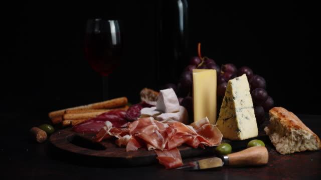vídeos de stock, filmes e b-roll de antipasto, queijo e vinho giram lentamente sobre a mesa. - comida italiana